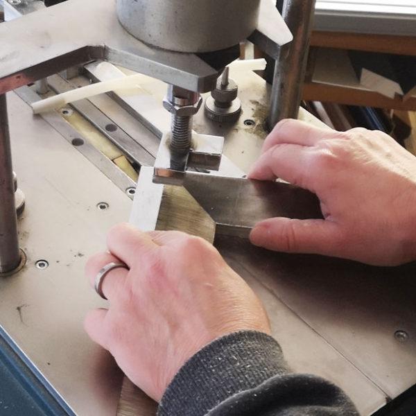 Mani in primo piano che lavorano ad una cornice